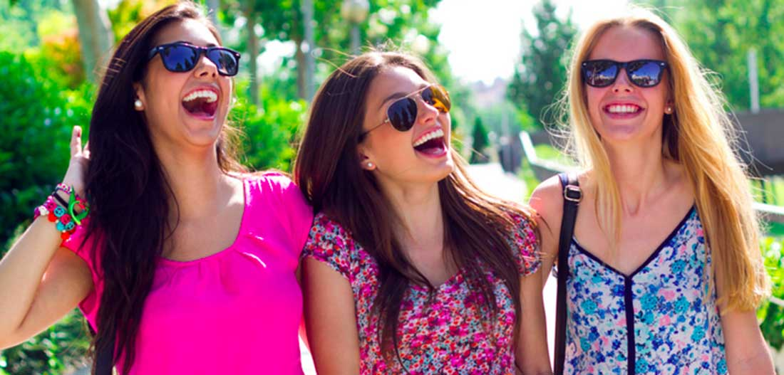 Three female students with sunglasses and summer dresses